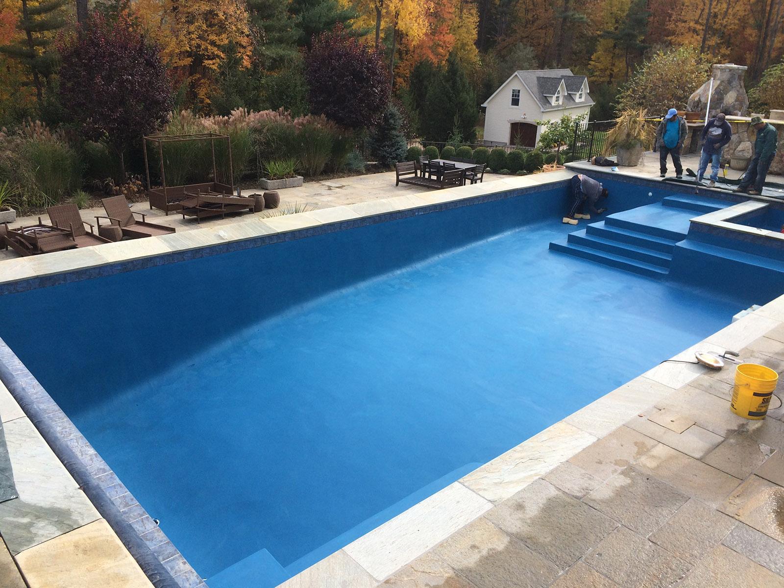 workers renovating inground swimming pool