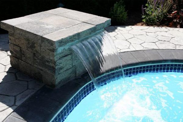 inground swimming pool with water feature