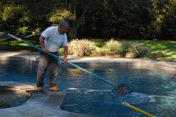 worker cleaning inground swimming pool