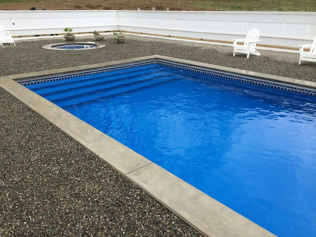 inground swimming pool and spa in backyard