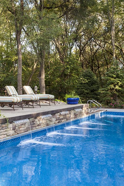 inground swimming pool in backyard with water feature