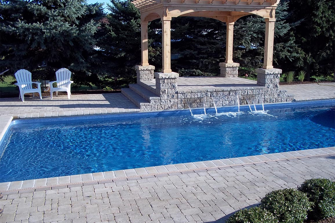 inground swimming pool with pergola and water feature