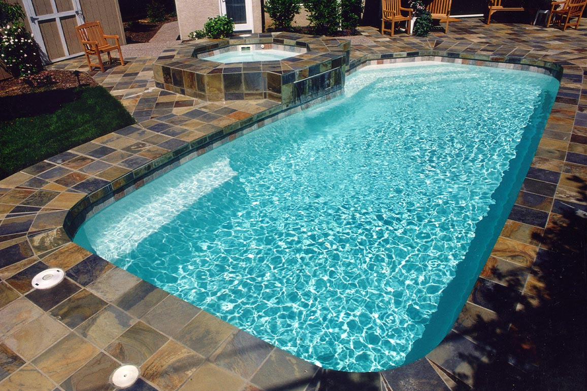 inground swimming pool with slate tile deck and spa