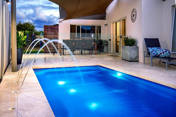 inground swimming pool with water feature and lights